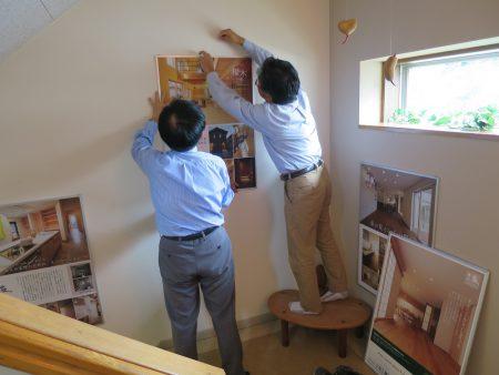 ▲仕事の合間を縫って掲示係をする社長と有村さん。パネルがまっすぐかかっているかどうかの確認が難しい!